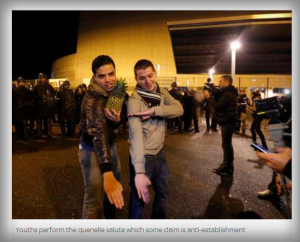 Growing racist anti-Jewish community movement performing the quenelle salute, pointing the right arm downwards at 45 degrees and placing the opposite hand on the arm.