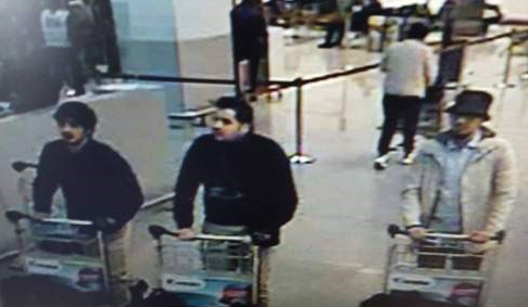 Brussels Airport terrorist attackers. The two men, on the left of the picture in black costumes, with dark hair would have died when they their parcel bomb exploded. The third man his luggage on the trolley did not explode. He got away and became the police target for March 2016